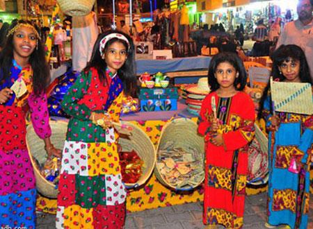 فتيات يرتدين الزي الشعبي التقليدي في سوق الأسر المنتجة